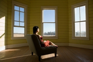 Woman sitting in sunbeam, looking out the window